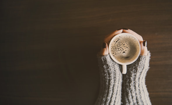 Girl holding a cup of coffee in winter