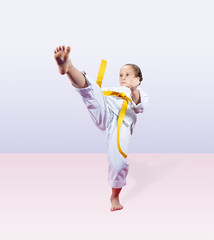 With yellow belt the sportswoman beats a kick leg forward