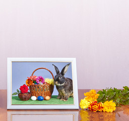On a light background a photo in frame with a picture of the Easter basket and bunny
