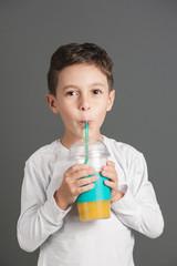 Little funny boy drinking a fresh juice through a straw