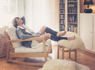 Frau mit Tablet sitzt gemütlich im Wohnzimmer vorm Fenster