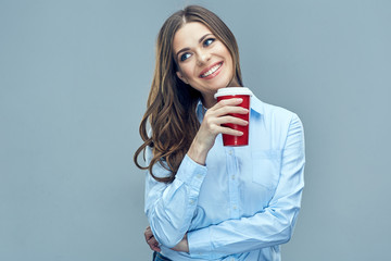 Smiling business woman holding red coffee glass looking to side.