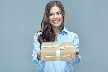Smiling business woman holding paper gift box.