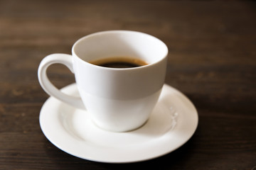 A white cup of black coffee on the wooden table. Selective focus, small depth of fieild.