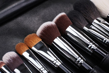 Makeup brushes set on black leather background