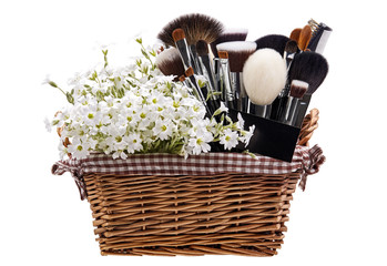 Makeup brushes set in crib with flowers. Chickweed. Isolated. Wh