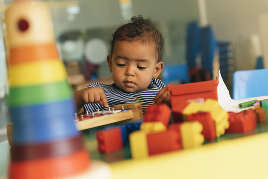 Happy baby playing with toy blocks.