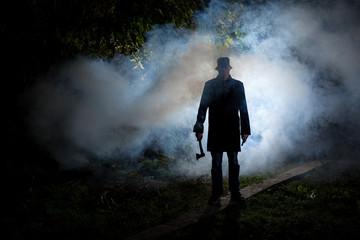 spooky man wih axe in the dark smoke filled forest