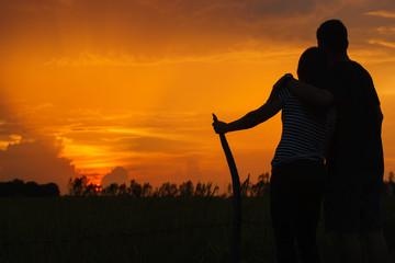 Silhouettes of hugging couple against the sunset sky at the fiel