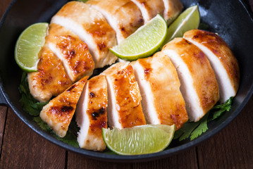 Sliced grilled chicken breasts with lime and parsley on dark wooden background close up. Healthy food.