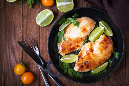 Chicken breasts with lime and parsley on dark wooden background top view. Healthy food. Nutritious meal.