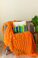 Skeins of wool lying in a white basket. Orange knitted blanket.