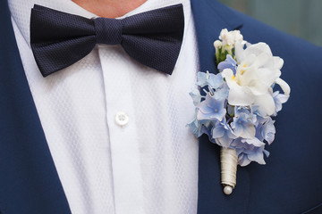 Blue and white boutonniere in blue suit of the groom