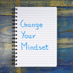 Change Your Mindset text written in notebook on wooden background