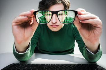 Nerdy guy with green data flow in his glasses