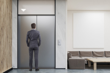Man waiting for elevator in company lobby