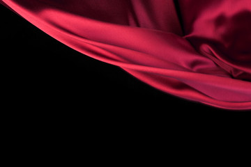 Red Fabric Cloth Flowing on Wind, Textile Wave Flying In Motion. Isolated on Black background