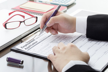 Businessman or job seeker fill in Employment Application form with pen. job vacancy concept.