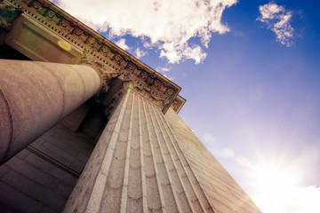 Upward view of a court house with impressive pillars. Morning sun shining down creating a beautiful lens flare. Architectural, construction, law, education and career concept Wall mural