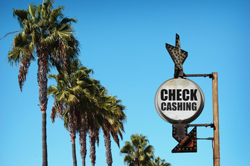 aged and worn vintage photo of check cashing sign and palm trees