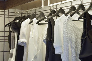 Black and white cloths hanging in closet