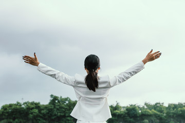 Woman breathing deep fresh air and outstretched arms  in summer