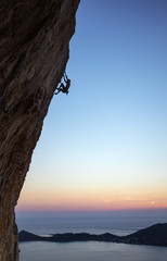 Rock climber on overhanging cliff at sunset. Kalymnos Island, Greece.