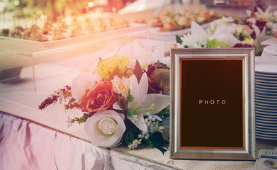 vintage blank frame and flower on table in wedding day