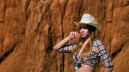 Young beautiful girl in cowboy clothes standing on background of the slope of the grand canyon.