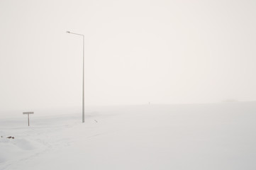 Street Lamp on a Foggy and Snowy Hill