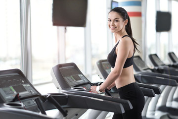 Delighted girl running on treadmill in a gym