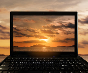 Close-up Black Laptop with landscape sunset at tropical ocean island on screen