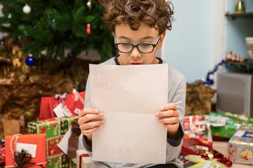 Bambino che legge la lettera di Babbo Natale