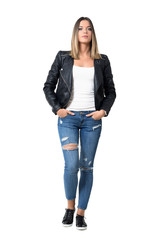 Confident serious gorgeous beauty in casual clothes with hands in pocket looking at camera. Full body length portrait isolated over studio white background.