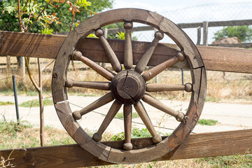 Old wooden wheel decorates the fence.