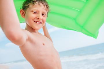 Smiling boy sea portrait with green air swiming mattress