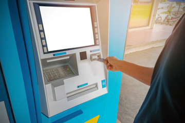 A man uses an ATM card inserted into the ATM machine for cash.
