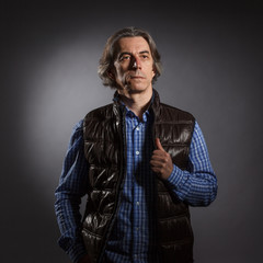 Artistic portrait of a man with long hair on dark background.