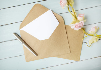 An open brown envelope with letter and writing pen on a blue wooden background