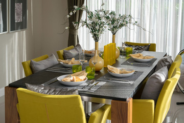 dining table and comfortable yellow chairs in modern home with elegant table setting