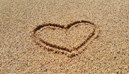 Drawing of abstract heart in the sand background