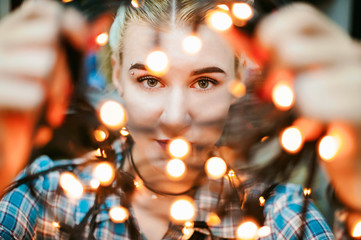 Portrait of a young woman with lights. beautiful girl with white hair dyed, looking through the Christmas lights