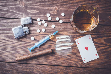 Hard drugs with pills, playing cards, syringe and alcohol on wooden table