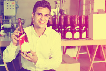 Man holding bottle of wine in packing section