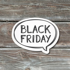 black friday lettering in speech bubble, handwritten text, paper sticker on realistic wood texture