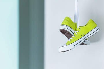 Pair of new green sneakers hanging on the wall