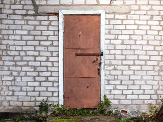 Old weathered barn door and brick wall.