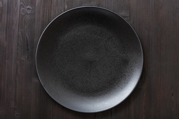 top view of black plate on dark brown table