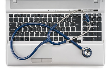 Stethoscope resting on computer keyboard - online medical support concept.