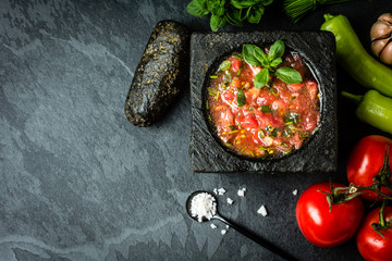 Tomato sauce salsa and ingredients dark stone background. Top view